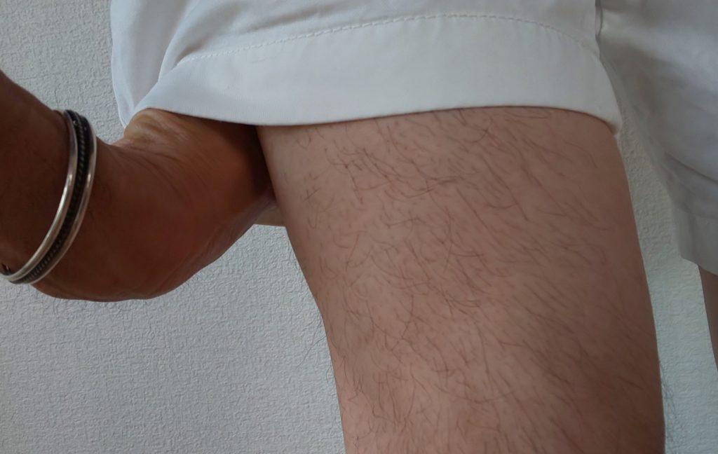 ショートパンツの下側から軽く握ったこぶしを入れている画像